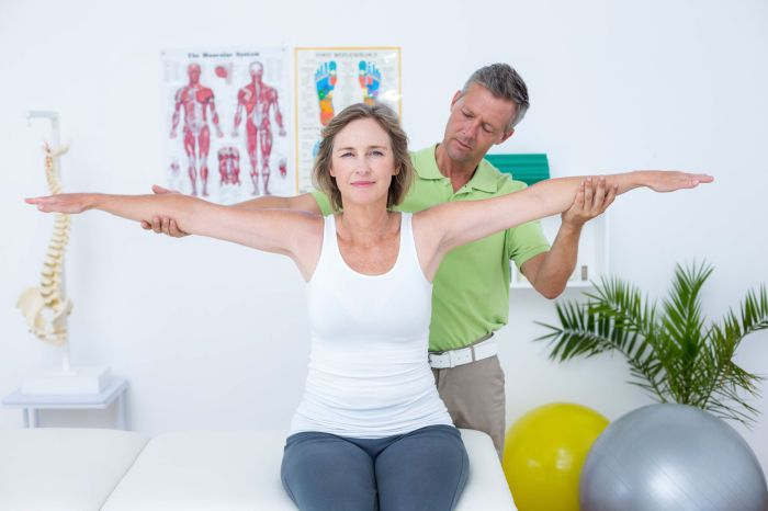 39828575 - doctor stretching his patients arms in medical office