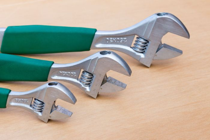 66093785 - three adjustable wrenches of different size standing upright on wood